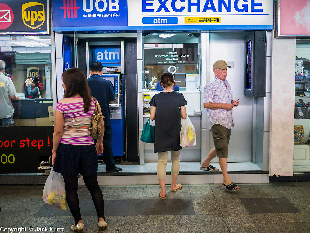 22 APRIL 2013 - BANGKOK, THAILAND:   People line up to buy Thai Baht at a foreign currency exchange kiosk in Bangkok. The Thai Baht has gained markedly against the US Dollar, the Euro and Pound Sterling in recent months. On Monday, the Baht was trading at 28.57 Baht to 1 US Dollar on Apr. 22. The strengthening Baht means imported goods are cheaper in Thailand, but Thai exports cost more in other countries. It also means tourists and expats who live in Thailand have less money to spend as their currencies buy fewer Baht. The baht has risen 5 percent against the dollar this year to its highest level since before the Asian financial crisis in 1997. The Federation of Thai Industries, which has led calls for the authorities to act to lower the baht, said the rise in the past two weeks had been too rapid and its members were finding it hard to cope with the volatility because as the Baht appreciates their exports become more expensive. Thailand is among the world's leading exporters of rice, chicken, pork, electrical components, cars and is the leading exporter of canned tuna.  PHOTO BY JACK KURTZ