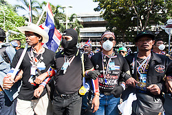 © Licensed to London News Pictures. 18/01/2014. Anti-Groverment Protesters march inside the Royal Thai Police Head quarters in response to an explosive device reportedly injuring as many as 30 people and killing one yesterday during an anti-government street rally in Bangkok, Thailand. Anti-government protesters launch 'Bangkok Shutdown', blocking major intersections in the heart of the capital, as part of their bid to oust the government of Prime Minister Yingluck Shinawatra ahead of elections scheduled to take place on February 2. Photo credit : Asanka Brendon Ratnayake/LNP
