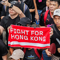 """A protester exhibits a towel that reads, """"Fight for Hong Kong"""" during the June protests in Hong Kong. Protesters are opposed to a controversial extradition bill."""