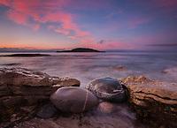 Colorful clouds light up at sunrise along the rocky coastline of Cape Breton island, Nova Scotia, Canada