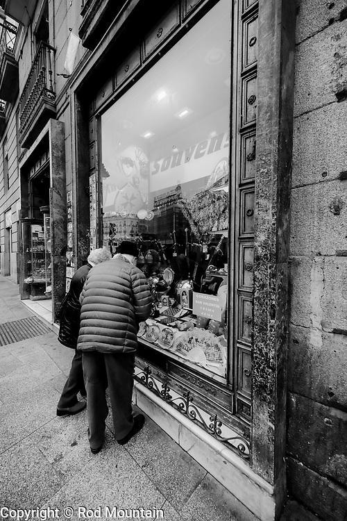 Madrid, Spain - February 15, 2018 - A tourist couple peering through the souvenir shop window near Puerta del Sol, Madrid, Spain.<br /> <br /> Image: © Rod Mountain <br /> http://www.rodmountain.com <br /> http://bit.ly/Madrid_bw<br /> Nikon D800 / Nikkor Lens <br /> <br /> @spain @visita_madrid @NikonUSA @nikoncanada @nikoneurope<br /> <br /> @spain.info @visitamadridoficial @NikonUSA @nikoncanada @nikoneurope<br /> <br /> @spain @Visita_Madrid @NikonUSA @nikoncanada @nikoneurope @TurismoMadrid<br /> <br /> https://en.wikipedia.org/wiki/Madrid<br /> https://www.spain.info/en/<br /> <br /> #TourismSpain #VisitSpain #wonderlust.spain #spain🇪🇸 #VisitMadrid #bnw_madrid #NikonCA #NikonNoFilter #NikonEurope #FriendsinBNW #friendsinstreets #bw_lover #bnw_demand #bnw_captures #bnw_life #bnw_city #bnwmood #bnw_planet #blackandwhiteisworththefight #friendsinperson #eyeshotmag #streets_storytelling #zonestreet #storyofthestreets #mySPC #streetscenesmag #photooftheday #capturestreets #bnw_demand #bnwmood