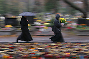 Lodz, Poland cemetery in the rain on All Saints Day. Nun and woman carrying flowers blurred in motion, created by panning. Nun run.