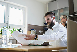 Young man with documents at the kitchen table and woman working in the background, Bavaria, Germany