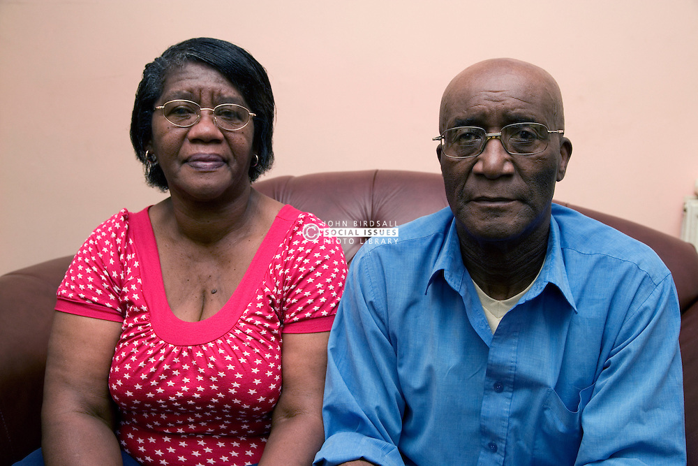 Older couple sitting on the sofa smiling,