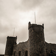 Overcast skies silhouette towers and walls at Harlech Castle in Harlech, Gwynedd, on the northwest coast of Wales next to the Irish Sea. The castle was built by Edward I in the closing decades of the 13th century as one of several castles designed to consolidate his conquest of Wales.