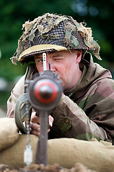 """A re-enactor from the Northern World War Two Association Living History group portrays a member of the British 5th Battalion, East Yorkshires, 50th Division complete with classic Brodie """"tin helmet"""" and PIAT (Projector, Infantry, Anti Tank)  antitank weapon SPAM 1940's Weekend Heckmonwyke near Wakefield 10 July 2010 .Images © Paul David Drabble."""