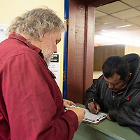 Andy Gorman, right, signs for a bus pass with Ken Collins, executive director of the Hozho Center at the center in Gallup Tuesday.