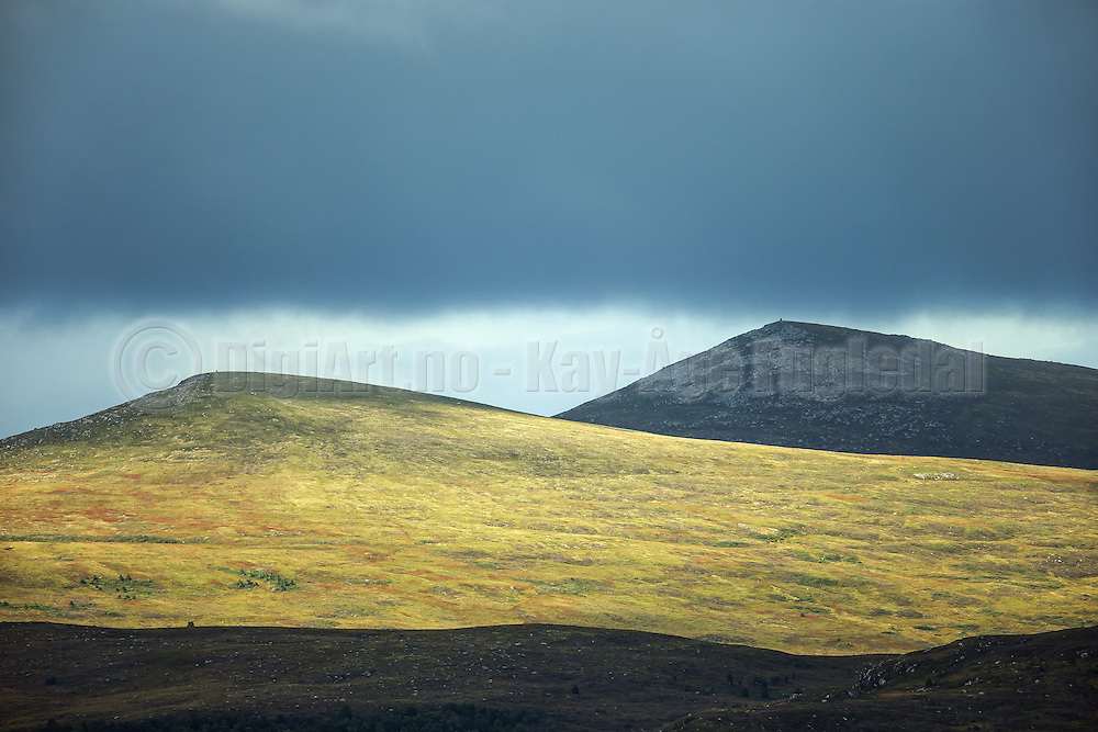 Montains partly lit by the sun, captured from far distance   Fjell som delvis er opplyst av solen, fotografert fra lang avstand.