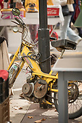 Old yellow mobylette scooter fastened to metal lamp post, France
