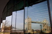The Victorian Tower Bridge is seen reflected in the large glass windows of City Hall, the HQ for the Mayor of London in the borough of Southwark. London's famous bridge was completed in 1894 and remains one of the capital's most visible symbols both for Victorian engineering and as a tourist landmark. The Mayor's Greater London Authority (GLA) headquarters stands over the Thames, opposite the Tower of London on the north shore.