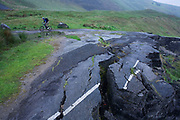 A wide landscape of damp hillsides and moorland as a lone cyclist struggles uphill near a road landslide at the foot of Mam Tor in the in the Derbyshire Peak District National Park. The bikers have struggled up this incline near the Blue John Cavern, a well-known location where visitors can descend into the cave system, one of many in this limestone and gritstone region of central England. The white lines of the highway have split as the tarmac drops away downhill. It's surface has been undermined as if seismic activity has occurred, an earthquake destroying this route high up in the mountains. But this is area is actually stable geologically and the slippage is probably caused by bad foundations and by recent heavy rain.