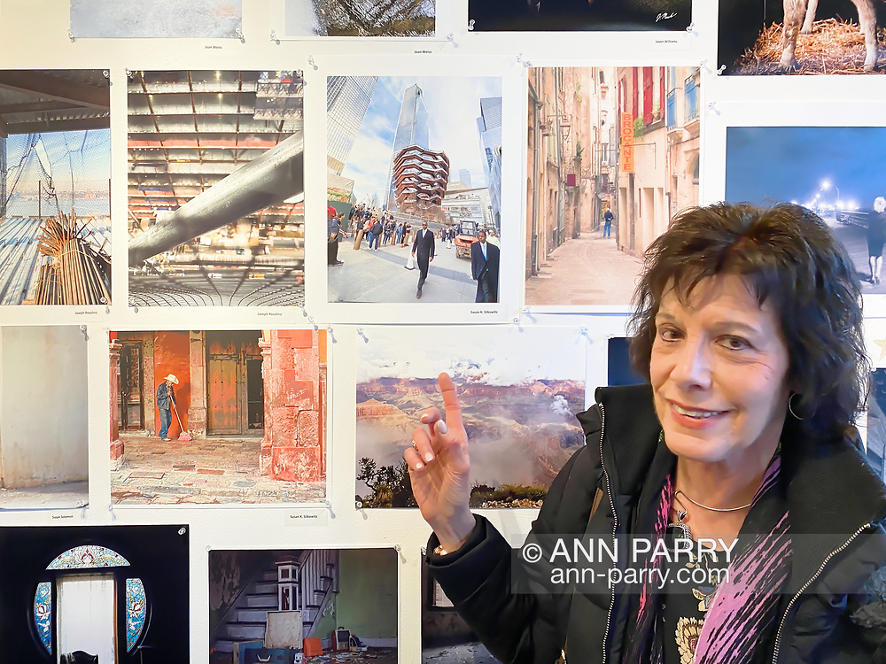 """Huntington, New York, U.S. February 29, 2020.  SUSAN K. SILKOWITZ points to her photo during fotofoto gallery reception for its """"Your Best Shot"""" Open Photography push-pin exhibition."""