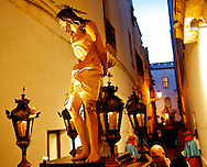 A wooden statue representing another moment of the passion of the Christ is carried through a narrow street