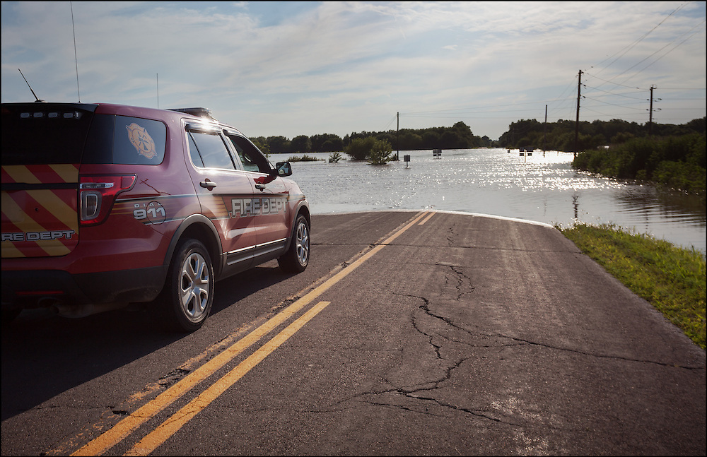 Captain of the Fire Department checking water height at the intersection of Highway E and Highway PP which is from rainfall from Northern Missouri that has flowed south affecting Carrollton, MO.