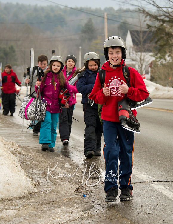 Elm Street School fifth graders make their way from Piches to Bolduc Park geared up for the winter sports of ice skating, cross country skiing and snowshoeing as part of learning about the winter Olympic Games on Thursday.  (Karen Bobotas/for the Laconia Daily Sun)