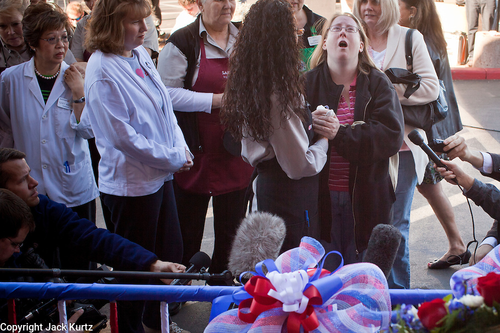 """15 JANUARY 2010 - TUCSON, AZ:    Safeway employees DAWN GALLAGHER (left, dark hair) comforts SHAYNE SPUDE (right) at the memorial for the victims of a a mass shooting in Tucson, AZ, Saturday, January 15, one week after the shooting. Six people were killed and 14 injured in the shooting spree at a """"Congress on Your Corner"""" event hosted by Arizona Congresswoman Gabrielle Giffords at a Safeway grocery store in north Tucson on January 8. Congresswoman Giffords, the intended target of the attack, was shot in the head and seriously injured in the attack but is recovering. Doctors announced that they removed her breathing tube Saturday, one week after the attack. The alleged gunman, Jared Lee Loughner, was wrestled to the ground by bystanders when he stopped shooting to reload the Glock 19 semi-automatic pistol. Loughner is currently in federal custody at a medium security prison near Phoenix.  PHOTO BY JACK KURTZ"""