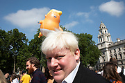 Boris Johnson lookalike and the Trump Baby, a six metre high inflatable blimp flying above the Houses of Parliament in Westminster prior to the Together Against Trump national demonstration on 13th July 2018 in London, United Kingdom. Organisations The Stop Trump Coalition and Stand Up to Trump have come together for a one-off national demonstration to protest against President Trump's policies and politics during his official UK visit.