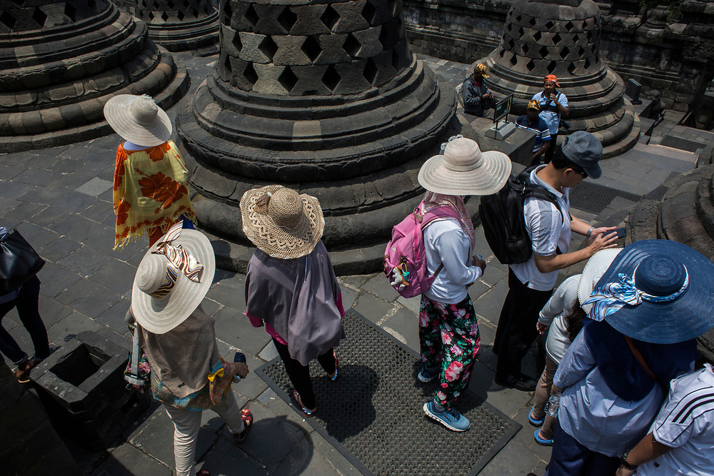 Tourists  photographing the stupas at Borobudur Temple in Magelang, Central Java, Indonesia. Borobudur is the largest Buddhist temple in the world built in the 9th-Century. Designated a UNESCO World Heritage Site in 1991, Borobudur remains Indonesia's most visited tourist attraction.