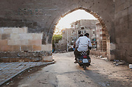 On a dusty street in an area of Cairo called the City of the Dead, two Egyptian men ride on a motorbike through an arched gate. The City of the Dead is a vast necropolis that is home to medieval tombs and mausoleums as well as a large living population. (April 26, 2010)