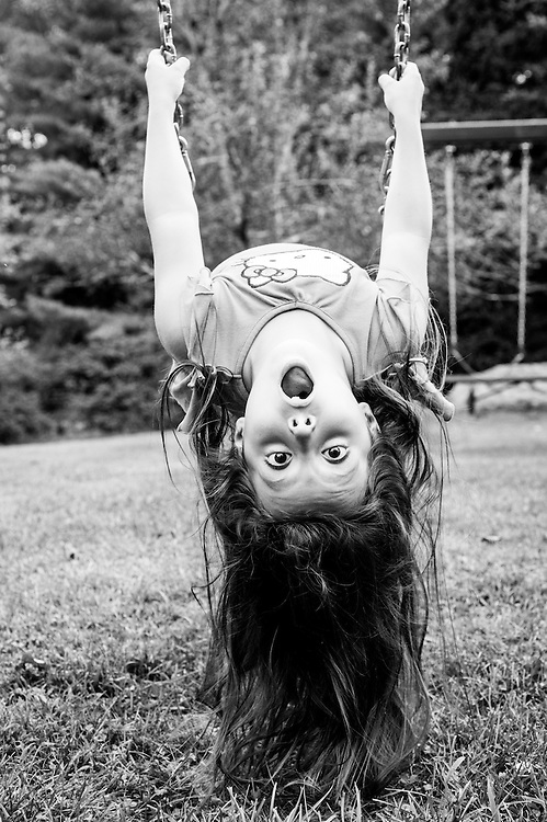 Young girl upside down on a swing in the Poconos, PA.