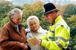 Policeman helping two elderly women Knaresborough Yorkshire UK