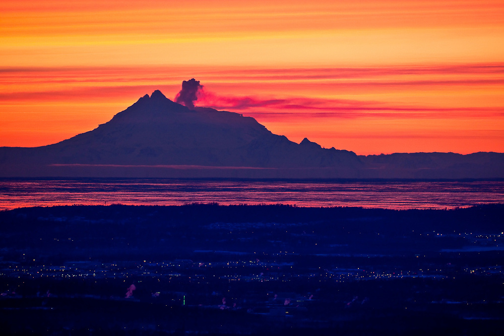 USA, Alaska.  Mount Redoubt in profile view from the northeast across Cook Inlet at sunset with large column of steam rising just below the peak of this active volcano in January.  Fata Morgana, an atmospheric mirage caused by a temperature inversion, is creating a distortion of the peak making it look much wider than it actually is .