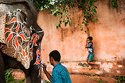 6th September 2014, New Delhi, India. An elephant handler decorates his elephant for an Indian wedding while a boy swings on a vine behind at New Rajinder Nagar, New Delhi, India on the 6th September 2014<br /> <br /> Elephant handlers (Mahouts) eke out a living in makeshift camps on the banks of the Yamuna River in New Delhi. They survive on a small retainer paid by the elephant owners and by giving rides to passers by. The owners keep all the money from hiring the animals out for religious festivals, events and weddings, they also are involved in the illegal trade of captive elephants.<br /> The living conditions and treatment of elephants kept in cities in North India is extremely harsh, the handlers use the banned 'ankush' or bullhook to control the animals through daily beatings, the animals have no proper shelters are forced to walk on burning hot tarmac and stand for hours with their feet chained together. <br /> <br /> PHOTOGRAPH BY AND COPYRIGHT OF SIMON DE TREY-WHITE + 91 98103 99809<br /> email: simon@simondetreywhite.com<br /> Photographer in Delhi