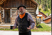 An actor plays Billy Barker in Barkerville Historic Town & Park, British Columbia, Canada. Historically the main town of the Cariboo Gold Rush, Barkerville is now the largest living-history museum in Western North America. The town was named after Billy Barker from Cambridgeshire, England, who struck gold here in 1861, and his claim became the richest and the most famous. This National Historic Site nestles in the Cariboo Mountains at elevation 1200m (4000ft), at the end of BC Highway 26, 80 kilometres (50 mi) east of Quesnel. Gold here was first discovered at Hills Bar in 1858, followed by other strikes in 1859 and 1860. Wide publication of these discoveries in 1861 began the Cariboo Gold Rush, which reached full swing by 1865 following strikes along Williams Creek. To license this Copyright photo, please inquire at PhotoSeek.com.