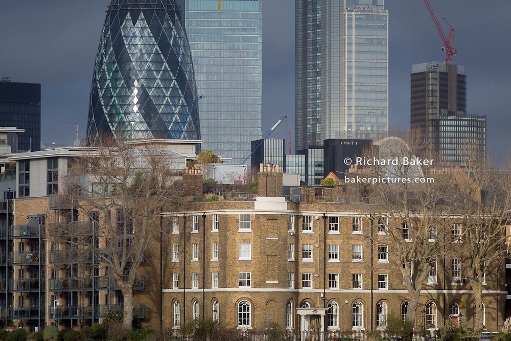 Tall financial properties in the City of London including the Swiss Re building, left,  (aka the Gherkin) rise above modern riverside residential apartments and the terrace of former dock officials' houses (designed by Daniel Asher Alexander) at Wapping Pierhead, built in 1811–13, on 17th January 2020, in London, England.