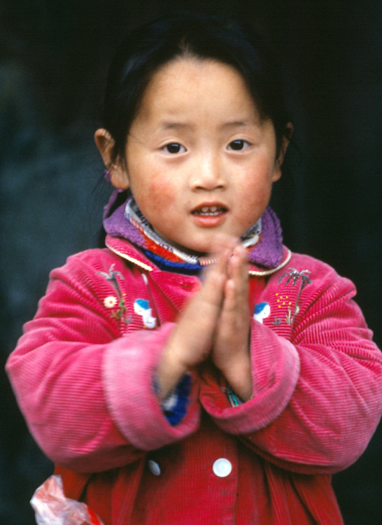 A girl in a pink jacket claps her welcome in Suzhou, China.