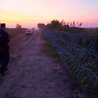 Police officer inspects the razor wire border fence between Hungary and Serbia near Roszke (about 174 km South of capital city Budapest), Hungary on August 30, 2015. ATTILA VOLGYI