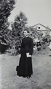 young priest with bible standing in the backyard of the church rural France 1950