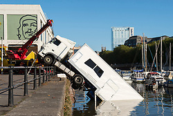 © Licensed to London News Pictures; 23/10/2021; Bristol, UK. Emergency services attend to an articulated lorry which has fallen into Bristol Harbour this morning, with the rear of the trailer in the water. It is reported that the lorry was carrying costumes for the filming of The Outlaws film series by Stephen Merchant. Photo credit: Simon Chapman/LNP.