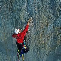 BAFFIN ISLAND, NUNAVUT, CANADA. Alex Lowe makes difficult hook moves, aid climbing high above Stewart Valley on Great Sail Peak. (MR)