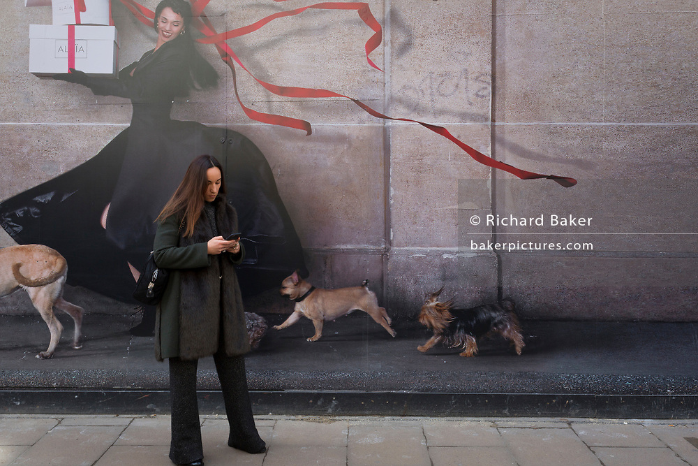 A lady pauses to check messages below a large construction hoarding for the retailer Alaia on New Bond Street, on 5th March 2018, in London, England.
