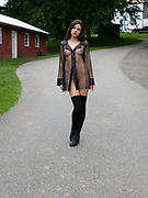 Nude woman wearing a black sheer top and black stockings standing in a driveway outside a barn