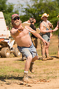 A competitor tosses a toilet seat in the red neck horseshoe contest during the 2015 National Red Neck Championships May 2, 2015 in Augusta, Georgia. Hundreds of people joined in a day of country sport and activities.