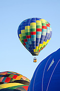 A brightly-coloured hot air balloon called 'Tracer' rises into a cloudless blue morning sky, Crown of Maine Balloon Fair, Presque Isle, Maine.