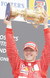 File photo dated 11-07-2004 of Ferrari's Michael Schumacher celebrates with the trophy after winning the British Grand Prix at Silverstone, Northamptonshire.