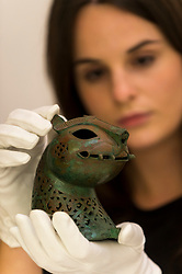 "© Licensed to London News Pictures. 23/10/2020. LONDON, UK. A staff member presents ""A Fine Cast Bronze Feline Head From An Incense Burner"", Khurasan Or Afghanistan, 11th-12th Century, (Estimate GBP15,000-20,000), at Sotheby's, New Bond Street during the preview of their auction of Treasures from the Islamic World on October 27.  Photo credit: Stephen Chung/LNP"