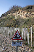 Crumbling cliffs and Danger sign for Unstable cliffs Dunwich beach and cliffs, North Sea coast, Suffolk, East Anglia, England