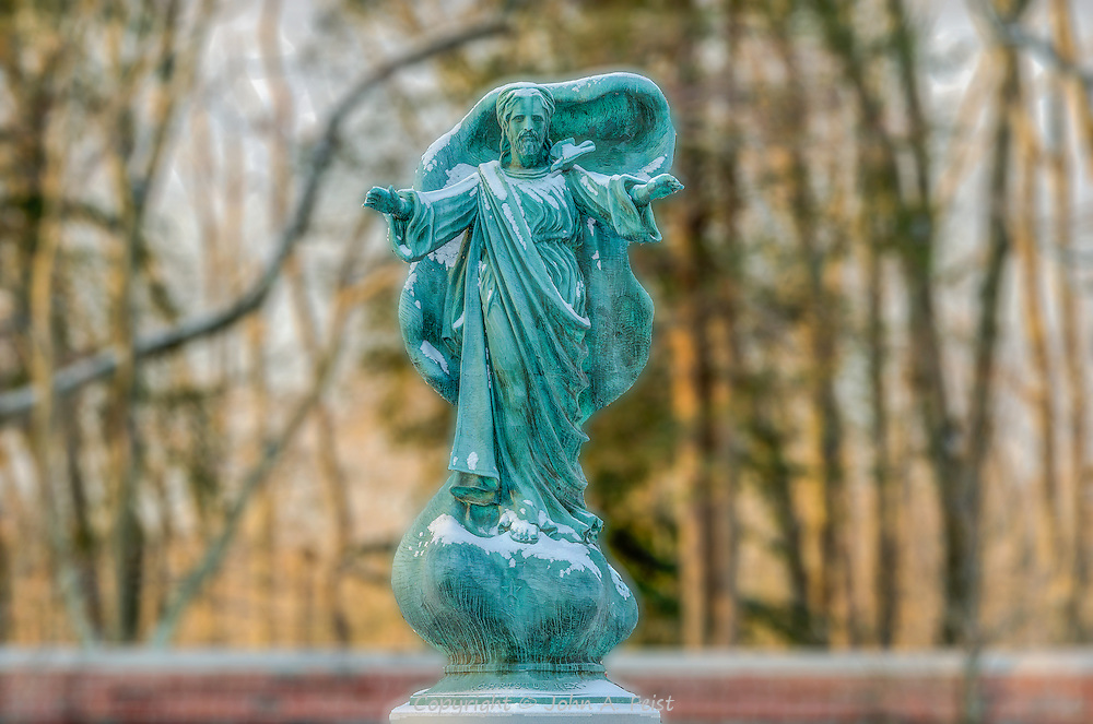 This statue stands in a prayer garden at Loyola House of Retreats in Morristown, NJ.  The statue is inspiring and humbling.  I took this shot early on a winter morning to get the beautiful golden background.