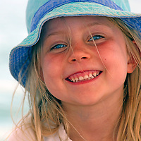 Girl with hat and whispy blonde hair blowing in breeze.