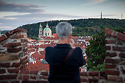 A woman watching the Lesser Town from Prague Castle. The Church of Saint Nicolas in the back.