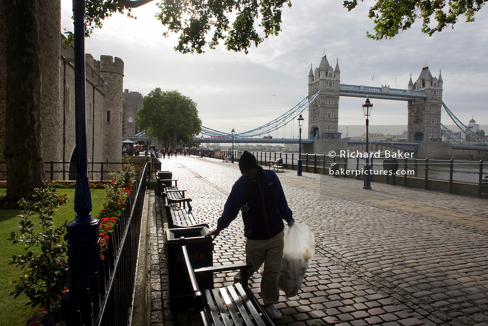In early morning light shines over Victorian cobbles, a rubbish collector checks the contents of bins at the Tower of London.