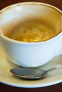 An empty cup of cappuccino and spoon in an Italian Cafe.