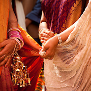 During a Hindu wedding in Delhi, a knot is tied between the bride's duppata (scarf) and the groom's scarf to symbolize the bond between them.