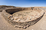 Casa Rinconada, occupied about AD 1140-1200, is an isolated great kiva (out of four in Chaco Canyon), built 63 feet (19 m) in diameter with a circular inner bench, masonry firebox, masonry vaults, 34 niches, four large pits for seating roof supports, plus an unusual 39-foot (12 m) passage dug underground through sandstone and shale. Chaco Culture National Historical Park hosts the densest and most exceptional concentration of pueblos in the American Southwest and is a UNESCO World Heritage Site. Chaco Canyon is in remote northwestern New Mexico, between Albuquerque and Farmington, USA. From 850 AD to 1250 AD, Chaco Canyon advanced then declined as a major center of culture for the Ancient Pueblo Peoples. Chacoans quarried sandstone blocks and hauled timber from great distances, assembling fifteen major complexes that remained the largest buildings in North America until the 1800s. Climate change may have led to its abandonment, beginning with a 50-year drought starting in 1130. This panorama was stitched from 13 overlapping photos.