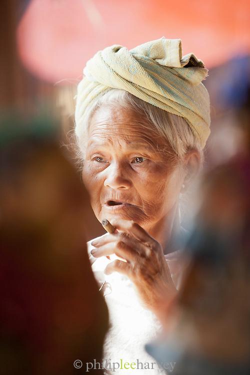 Elderly woman smoking cheroot (cigar), Myanmar
