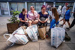 © Licensed to London News Pictures. 15/06/2020. London, UK. Young shoppers have a rest after a day of shopping in Kingston, South West London as non essential shops are given the green light to open in England after 3 months of being closed due to the coronavirus pandemic. Also commuters are told to wear face masks from Monday while travelling on Public transport. Photo credit: Alex Lentati/LNP